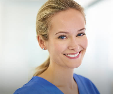 Smiling woman in hospital scrubs