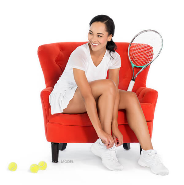 Model on red chair with tennis racket